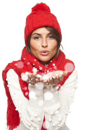 Woman wearing knitted warm red scarf and hat blowing snow at you, looking at camera, over white background
