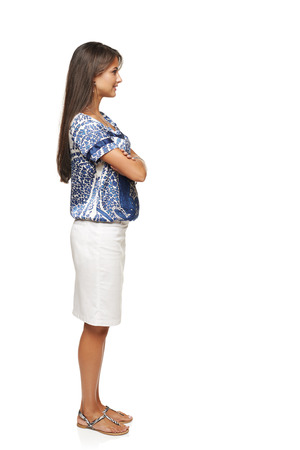 Full length side view business woman standing with folded hands and looking forward, isolated on white background