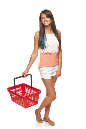full length woman: Shopping concept. Happy full length woman walking with empty red shopping basket, white background Stock Photo
