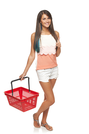 full length woman: Shopping concept. Happy full length woman walking with empty red shopping basket and gesturing thumb up, white background Stock Photo