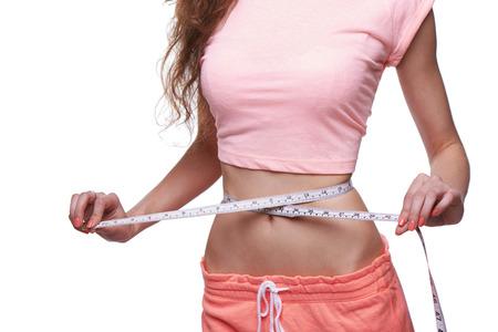 cuerpo femenino perfecto: Mujer que mide su cuerpo delgado aislado en fondo blanco. Imagen recortada.