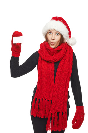 Christmas shopping. Suprised woman wearing santa hat and red scarf and mittens showing blank credit card, over white background photo