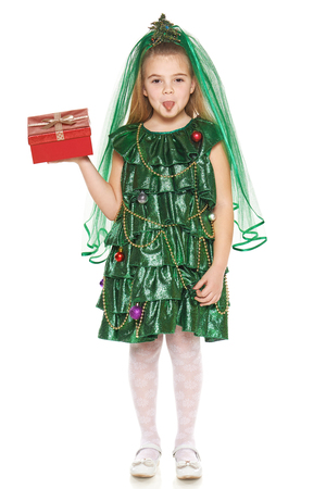 Little girl in Christmas tree costume pulling face showing tongue holding red gift box standing in full length, over white background photo
