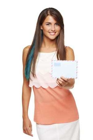 outstretching: Trendy young smiling woman giving you blank envelope, over white background. Shallow depth of field, focus on envelope Stock Photo