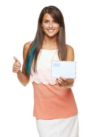 missive: Good news concept. Trendy young smiling woman giving you blank envelope and gesturing thumb up, over white background. Shallow depth of field, focus on envelope