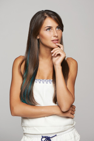 envisioning: Thinking funky young female with blue hair lock standing with folded hands and looking away at blank copy space, over gray background