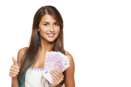 ユーロのお金を手に白い背景の上のサインアップでは、親指を身振りで示すと若い美しい女性のクローズ アップ