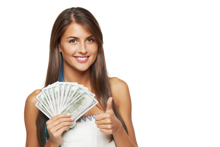 Closeup of young beautiful woman with us dollar money in hand gesturing thumb up, over white background, with copy space