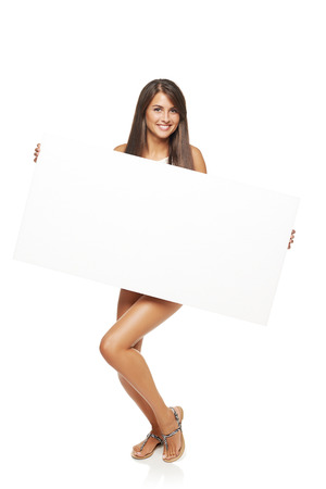 nude woman standing: Full length happy woman standing holding white board banner over white background