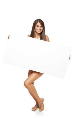 donna nudo: Tutta la lunghezza donna felice in piedi tenendo bordo bianco banner su sfondo bianco