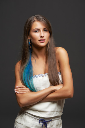 colored dye: Portrait of happy smiling funky young female with blue hair lock, over dark background Stock Photo