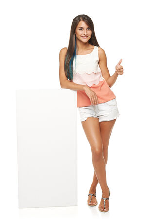 Full length of beautiful tanned woman in shorts standing leaning on white blank advertising board banner and showing approving sign, over white background photo
