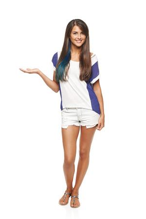 mujer cuerpo completo: Longitud total de una hermosa mujer curtida en pantalones cortos que muestran que sostiene en la palma espacio de la copia en blanco sobre fondo blanco Foto de archivo