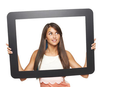 Smiling young woman looking to side through tablet frame, over white background photo