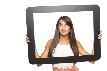 Smiling young woman looking to side through tablet frame,\ over white background