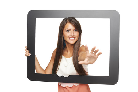 attempting: Beautiful smiling woman peeping through tablet frame and stretching her hand attempting to grab you, over white background