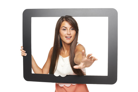 attempting: Beautiful smiling woman peeping through tablet frame and stretching her hand attempting to grab something, over white background