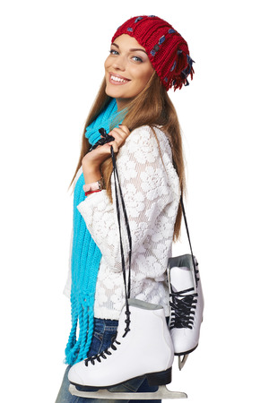 ice skating: Smiling young woman carrying a pair of ice skates over white background Stock Photo
