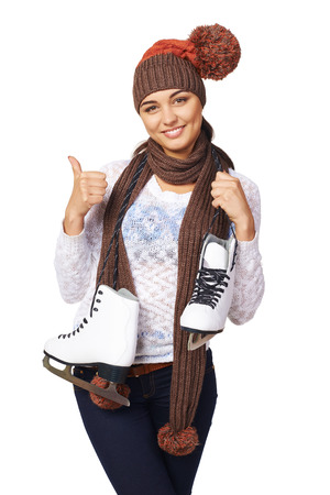 iceskates: Smiling young woman wearing warm hat and scarf carrying a pair of ice skates and gesturing thumb up, over white background