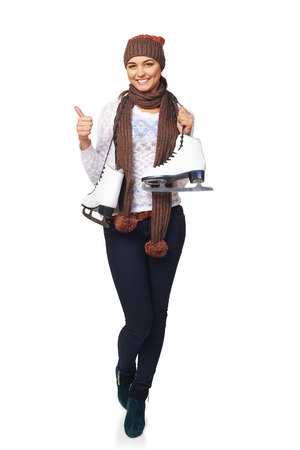posing  agree: Full length of smiling young woman wearing warm hat and scarf carrying a pair of ice skates and gesturing thumb up, over white background