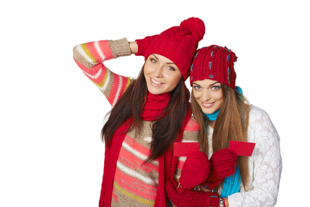 Two beautiful girls wearing winter hats, mufflers and gloves showing blank red cards photo