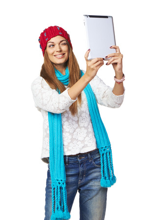 Happy smiling young woman wearing winter clothing taking pictures of herself through digital tablet, over white background photo