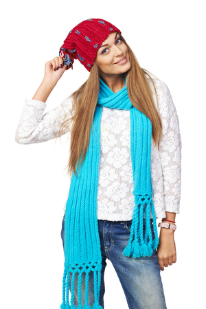 pompon: Playful beautiful woman in red hat and blue scarf playing with pompon, over white background