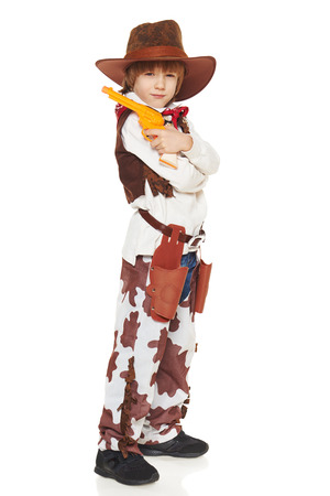 Full length of serious little boy in a suit of the cowboy posing with guns, on a white background photo