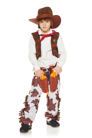 Full length of little boy in a suit of the cowboy posing with guns, on a white background