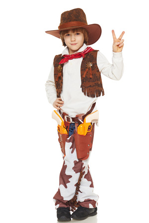 Full length of little boy in a suit of the cowboy showing victory sign, on a white background photo