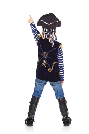 Full length back view of little boy wearing pirate costume standing over white background and pointing up photo