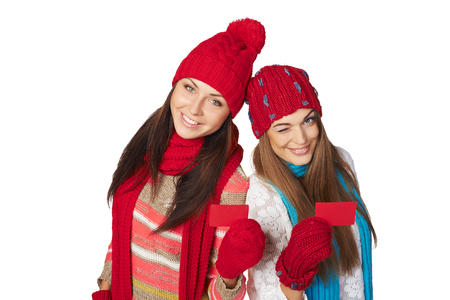 Two beautiful girls wearing winter hats, mufflers and gloves showing blank red cards over white background, high angle view photo