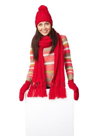 outerwear: Donna felice esterno in inverno in piedi dietro e appoggiata sul banner bianco in studio su sfondo bianco