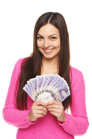Closeup of young beautiful woman with British pounds in hand