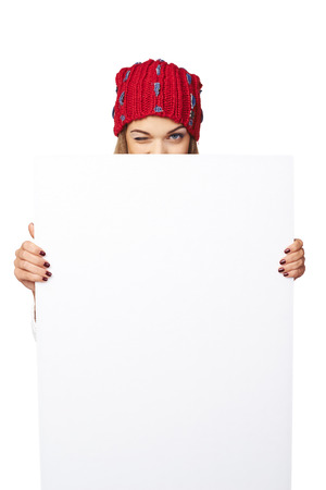 winking: Smiling happy woman in winter hat peeking out of the edge of white banner and winking over white studio background