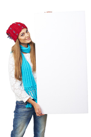 Smiling happy woman in winter hat holding white banner over white studio background photo
