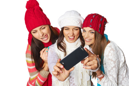 three persons: Friends making selfie. Three beautiful young women wearing warm winter clothing making selfie