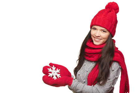 Closeup of smiling woman wearing red winter hat, scarf and mittens holding white big snowflake over white background photo