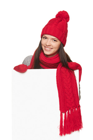 Smiling happy woman in red winter hat, scarf and gloves holding standing behind of white banner over white studio background Stock Photo