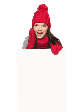 Happy surprised woman in red winter hat, scarf and gloves holding white banner, over white studio background photo