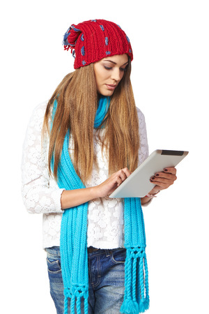 Winter woman wearing warm knitted hat and scarf using digital tablet isolated on white background photo