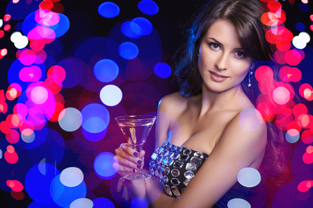 Holidays, christmas, people celebration concept. Closeup of woman in evening dress with glass over holidays lights bokeh background