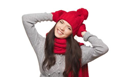 女性の身に着けている赤い冬の帽子、スカーフ、ミトンの手で頭の上、白い背景の上を楽しんで笑みを浮かべてください。 写真素材