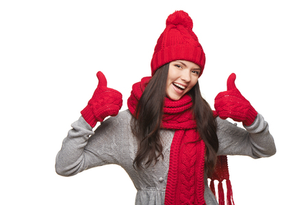 Closeup of happy woman wearing red warm winter hat, scarf and gloves giving you double thumb up, over white background photo