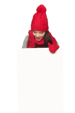 Happy surprised woman in red winter hat, scarf and gloves holding white banner, looking at it, over white studio background photo