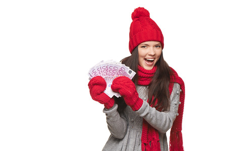 Happy excited winter woman holding euro cash money, over white background, with copy space photo