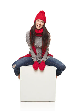 large woman: Winter woman wearing knitted warm red scarf and hat sitting on big white box, over white background