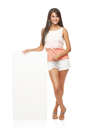 board shorts: Full length of beautiful tanned woman in shorts standing leaning on white blank advertising board banner and pointing at it Stock Photo