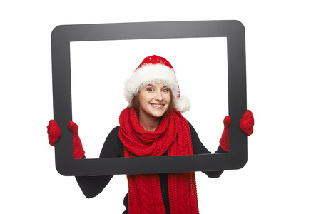 Smiling girl in Santa hat looking from TV computer screen, isolated on white background. photo