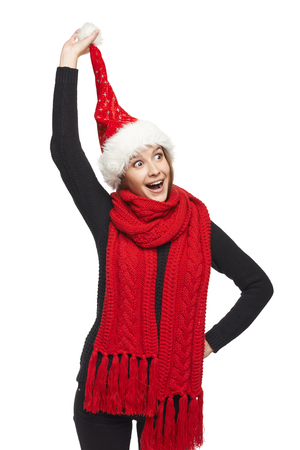 pompon: Funny Christmas woman surprised wearing Santa hat pulling her Santa hat pompon, looking at camera with mouth open in amazement